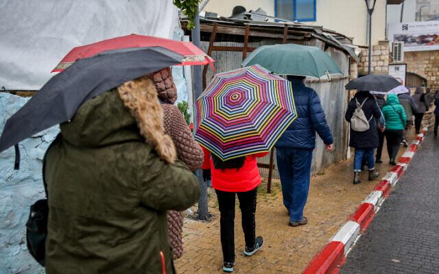 Les gens marchent sous la pluie à Tsfat, le 9 décembre 2019. (Crédit : David Cohen/Flash90)