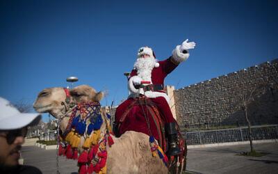 Un homme déguisé en Père Noël chevauche un chameau à la porte de Jaffa dans la Vieille Ville de Jérusalem, pendant la distribution d'arbres de Noël et quelques jours avant la prochaine fête de Noël, le 19 décembre 2019. (Yonatan Sindel/Flash90)