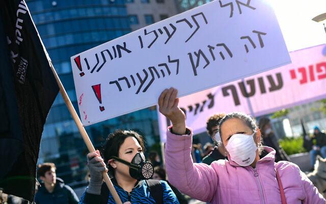 """Des écologistes israéliens protestent contre le test de purge de la plate-forme de gaz de Noble Energy, devant le bâtiment du ministère de la Défense à Tel Aviv, le 31 décembre 2019. La pancarte dit: """"Ne nous empoisonnez pas, c'est le moment de vous réveiller"""". (Crédit : Tomer Neuberg/Flash90)"""