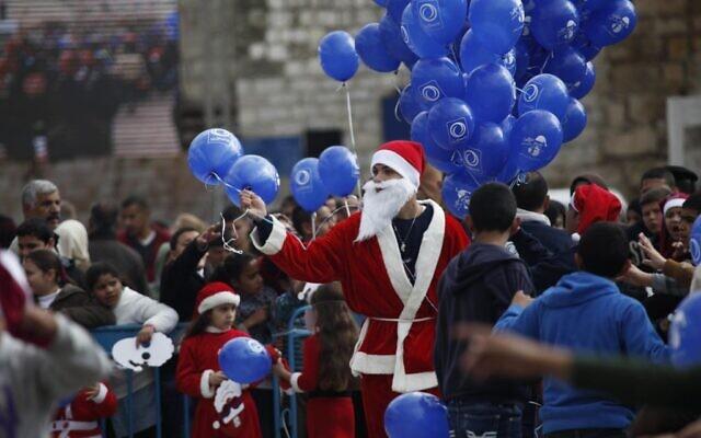 Un Palestinien déguisé en père Noël tient des ballons aux abords de l'église de la Nativité à Bethléem, en Cisjordanie, à la veille de Noël, le 24 décembre 2014 (Crédit : AP Photo/Majdi Mohammed/File)