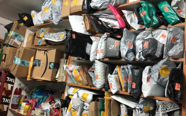 Des étagères remplies de paquets dans une makolet de Jérusalem qui est payée pour traiter les paquets des clients, 22 décembre 2019. (Crédit : Jessica Steinberg/Times of Israel)