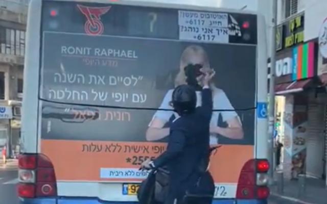 Un ultra-orthodoxe vandalise une affiche de publicité où figure une femme sur un bus, des images parues le 8 décembre 2019 (Capture d'écran : Twitter)