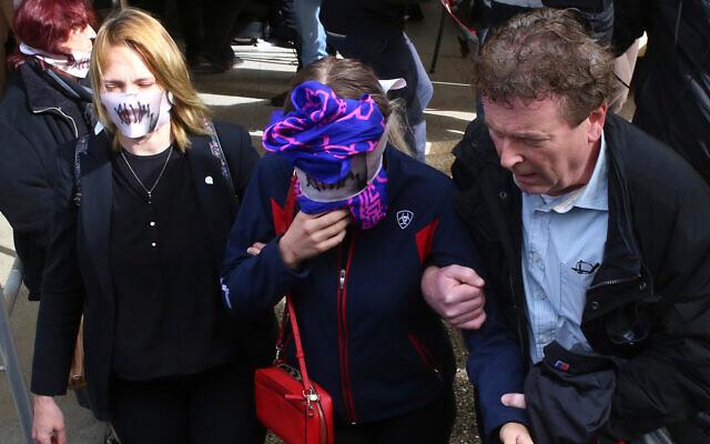 Une Britannique de 19 ans, au centre, se couvre le visage en quittant le tribunal de Famagouste après son procès, à Paralimni (Chypre), le 30 décembre 2019. (Crédit : AP/Philippos Christou)