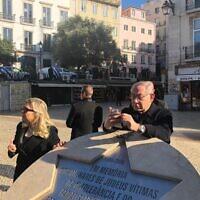 Le Premier ministre Benjamin Netanyahu consulte son téléphone en s'appuyant sur un mémorial d'un pogrom qui a fait des centaines de victimes juives à Lisbonne en 1506, le 5 décembre 2019. (Crédit : Shalom Yerushalmi/Zman Yisrael)