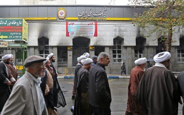 Des Iraniens passent devant une agence bancaire locale qui a été dégradée lors des manifestations contre la hausse des prix du pétrole le 20 novembre 2019 à Shahriar, à l'ouest de Téhéran. (Photo par ATTA KENARE / AFP)