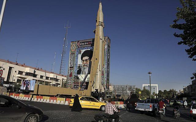 """Un missile sol-sol Shahab-3 est exposé à proximité d'un portrait du guide suprême iranien l'Ayatollah Ali Khamenei lors d'une présentation de l'armée iranienne et du groupe paramilitaire des Gardiens de la Révolution célébrant la """"Semaine de défense sacrée"""" qui marque le 39ème anniversaire du début de la guerre Iran-Iraq de 1980 à 1988, sur la place Baharestan dans le centre ville de Téhéran, en Iran, le 25 septembre 2019. (Crédit : AP/Vahid Salemi)"""