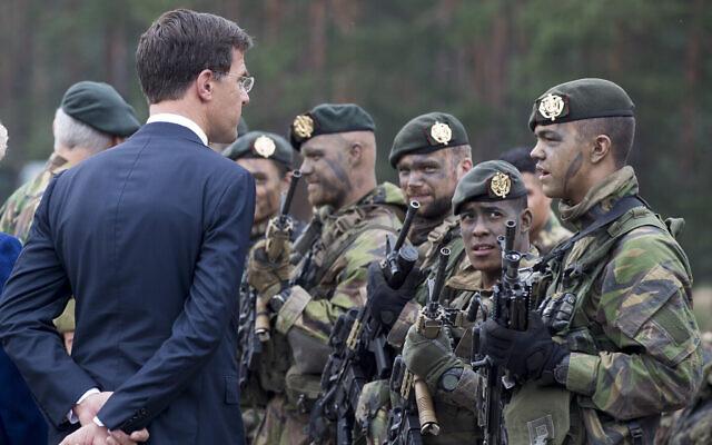 Le Premier ministre hollandais Mark Rutte parle à un soldat hollandais d'un bataillon de présence renforcée de l'OTAN lors de la visite de la base militaire Rukla à environ 130 km à l'ouest de la capitale Vilnius en Lituanie le vendredi 11 août 2017. (AP Photo/Mindaugas Kulbis)