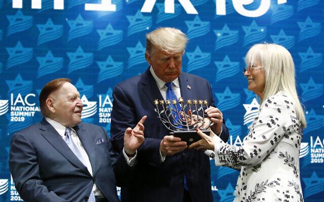 Le président Donald Trump reçoit une ménorah du directeur général de la Las Vegas Sands Corporation et grand donateur républicain Sheldon Adelson, à gauche, et de son épouse Miriam Adelson au sommet national du Conseil américain israélien à Hollywood, en Floride, le samedi 7 décembre 2019. (Crédit : AP Photo/Patrick Semansky)