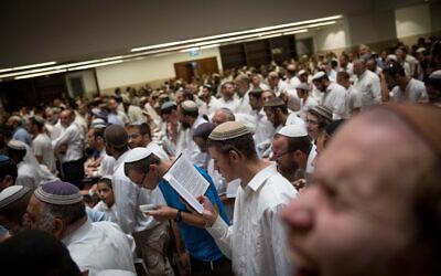 Des hommes juifs prient dans le mouvement bâtiment de la yeshiva Har Hamor Yeshiva dans le quartier d' Har Homa à Jerusalem le 22 août 2017. (Yonatan Sindel/Flash90)