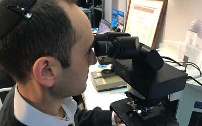 Augmentiqs a développé un appareil électro-optique qui s'intègre au sein d'un microscope déjà existant et le transforme en un objet connecté et intelligent. Le co-fondateur Gabe Siegel regarde au microscope à l'exposition HealthIL à Tel Aviv, le 27 novembre 2019. (Shoshanna Solomon/Times of Israel)