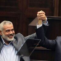 Ismail Haniyeh, le chef du Hamas dans la bande de Gaza (à gauche) et son homologue turc Recep Tayyip Erdogan saluent les élus et soutiens du parti islamique de la Justice et du Développement d'Ergodan au parlement à Ankara, en Turquie, le 3 janvier 2012. (Crédit : AP)