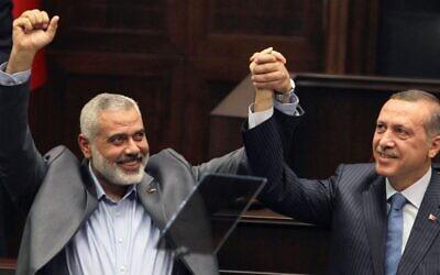 Ismail Haniyeh, le chef du Hamas dans la bande de Gaza, (à gauche), et son homologue turc Recep Tayyip Erdogan saluent les élus et soutiens du parti islamique de la Justice et du Développement d'Ergodan au parlement à Ankara, en Turquie, el 3 janvier 2012. (Crédit photo : AP)