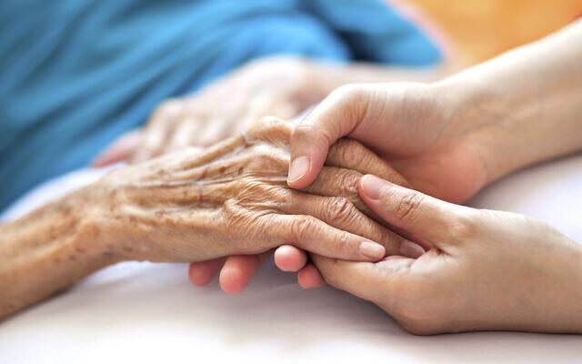 Illustration : Une femme tenant la main d'une femme âgée sur le lit. (Crédit :Pablo_K; iStock by Getty Images)