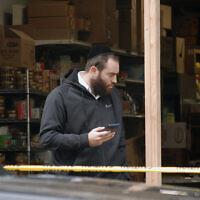 Un juif hassidique est devant le supermarché JC Kosher à Jersey City, N.J., lieu d'une fusillade qui a fait trois morts en plus des deux tireurs, le 11 décembre 2019. La police enquête toujours pour savoir s'il s'agit d'un crime haineux. (Laura E. Adkins/JTA News)
