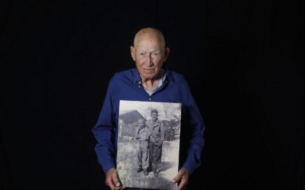Le survivant de la Shoah Danny Chanoch, 87 ans, montre une photo de lui t de son frère Uri après la guerre, à son domicile de Karmei Yossef, le 10 décembre 2019. (Crédit : MENAHEM KAHANA / AFP)