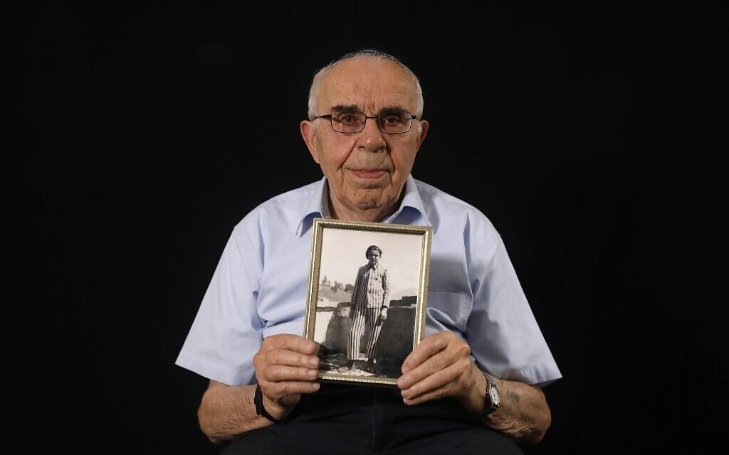 Le survivant de la Shoah Menahem Haberman, 92 ans, pose avec une photo de lui après la guerre, à son domicile de Jérusalem, le 12 décembre 2019. (Crédit : MENAHEM KAHANA / AFP)