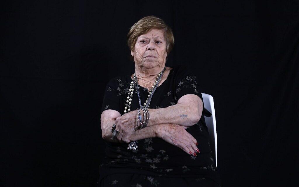 La survivante de la Shoah Malka Zaken, 91 ans, montre sa matricule 76979, à son domicile de Tel Aviv, le 16 décembre 2019. (Crédit :MENAHEM KAHANA / AFP)