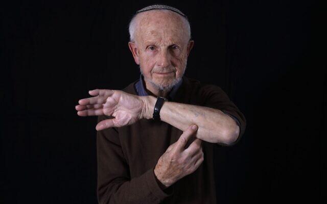 Saul Oren, survivant de la Shoah, montre son bras avec le numéro 125421 du camp d'Auschwitz, lors d'une séance photo à son domicile à Jérusalem le 2 décembre 2019. Né en Pologne en 1929, il a été choisi par un médecin nazi pour subir des expériences médicales et a été transféré d'Auschwitz vers un camp de concentration en Allemagne, pour être libéré en 1945. Après la guerre, il retrouva son frère qui avait été avec lui à Auschwitz et émigra en Israël. - En amont des événements marquant le 75e anniversaire de la libération d'Auschwitz, l'AFP s'est entretenue avec les derniers survivants du camp de la mort. Originaires d'Europe, ils ont passé une partie de leur enfance dans le célèbre camp d'extermination avant de s'installer en Israël après la Seconde Guerre mondiale. (MENAHEM KAHANA / AFP)