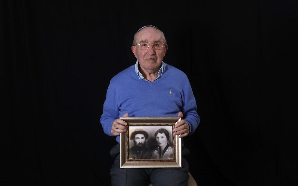 Le survivant de la Shoah Szmul Icek montre une photo de ses parents tués par les nazis, à son domicile de Jérusalem, le 8 décembre 2019. (Crédit : MENAHEM KAHANA / AFP)