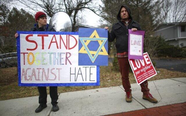 Des manifestants arborent des panneaux de soutien près de la maison du Rabbin Chaim Rottenberg le 29 décembre 2019 à Monsey, New York. (Photo de Kena Betancur / AFP)
