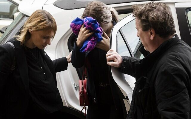 Une adolescente britannique accusée d'avoir prétendu à tort avoir été violée par des touristes israéliens, se couvre le visage alors qu'elle arrive pour son procès devant le tribunal de district de Famagouste à Paralimni, dans l'est de Chypre, le 30 décembre 2019. (Crédit : Iakovos Hatzistavrou / AFP)