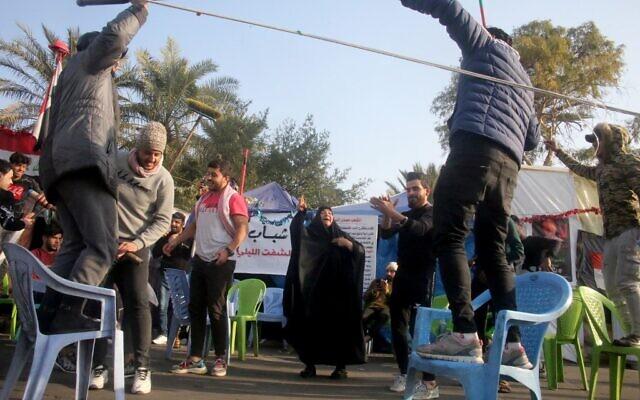 Des manifestants anti-gouvernementaux irakiens célèbrent devant leurs tentes sur la place Tahrir de Bagdad à la suite de la nouvelle du meurtre du commandant en chef des Gardiens de la révolution iraniens Qasem Soleimani. (Crédit : AFP)