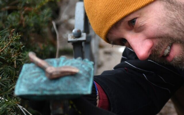 Le sculpteur Mihajlo (Mihaly) Kolodko et sa nouvelle sculpture de petite taille, la «hache», à proximité du monument soviétique de la Seconde Guerre mondiale sur la place de la Liberté à Budapest, en Hongrie, le 3 janvier 2020. (Crédit : Attila KISBENEDEK / AFP)