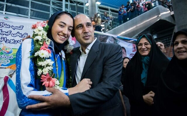 Kimia Alizadeh, la première Iranienne à avoir remporté une médaille olympique, est accueillie par son père Keivan Alizadeh (à droite) à son arrivée à l'aéroport international Imam Khomeini de la capitale Téhéran, le 26 août 2016. (Crédit : Peyman / ISNA / AFP)