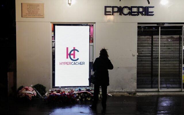 Une femme se tient devant le supermarché casher Hyper Cacher dans le sud-ouest de Paris le 9 janvier 2020 lors d'une cérémonie commémorative cinq ans après une prise d'otage mortelle par un homme armé djihadiste. (Crédit : Thomas SAMSON / AFP)