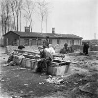 Sur cette photographie prise en avril 1945, des survivants du camp de concentration nazi de Buchenwald sont assis sur une latrine, après la libération du camp par les troupes alliées. (Crédit : Eric Schwab/AFP)