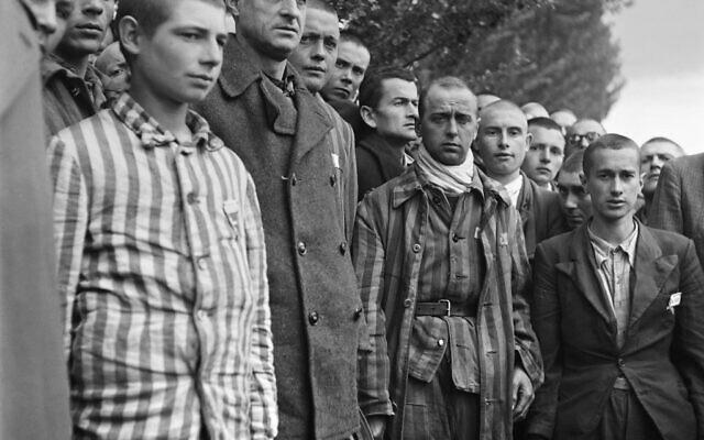Sur cette photographie prise le 29 avril 1945, des prisonniers français observent une minute de silence, lors de la libération du camp de concentration nazi de Dachau, près de Munich, par les troupes alliées. (Crédit : Eric Schwab / AFP)