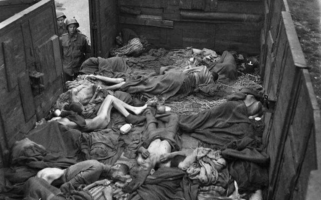 Sur cette photo prise le 1er mai 1945, des soldats américains regardent un tas de corps de prisonniers dans un train près du camp de concentration de Dachau, après que le camp a été libéré par l'armée américaine le 29 avril 1945. (Crédit : Eric Schwab / AFP)