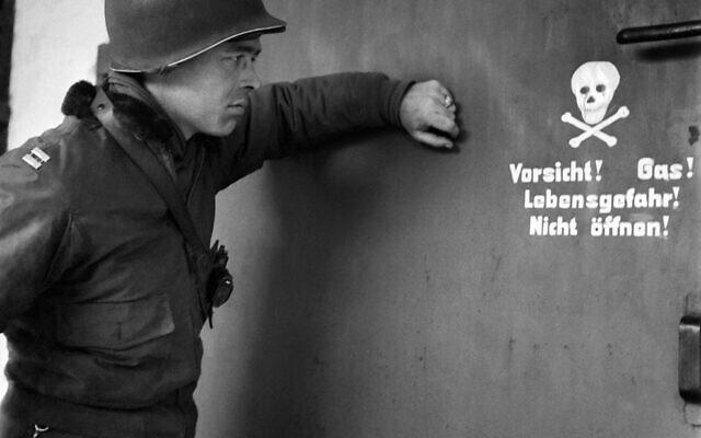 Sur cette photo prise le 29 avril 1945, un soldat américain regarde un panneau devant la porte d'une chambre à gaz du camp de concentration nazi de Dachau, lors de la libération du camp par les troupes alliées. (Crédit : ERIC SCHWAB / AFP)