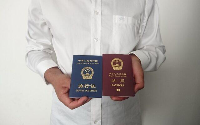 Sur une photo prise le 2 octobre 2019, on voit un homme ouïghour chinois non identifié dans la ville de Médine, tenant son passeport chinois expiré (rouge) et un document de voyage aller simple (bleu) délivré à sa place par la mission chinoise en Arabie Saoudite. (Crédit : AFP)