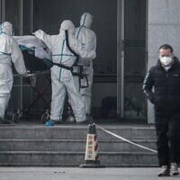 Des membres du personnel médical transportant un patient à l'hôpital de Jinyintan, où sont soignés des patients infectés par un mystérieux virus de type SRAS, à Wuhan, dans la province centrale du Hubei, en Chine, le 18 janvier 2020. (AFP)