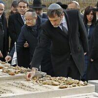 Le ministre français de l'Intérieur Christophe Castaner se rend sur les tombes des victimes de l'attentat de l'école Ozar Hatorah à Toulouse, au cimetière israélien de Givat Shaul à Jérusalem, le 23 janvier 2020. En arrière plan, Eva Sandler, qui a parti son mari et ses deux fils Aryeh et Gabriel lors de cette tuerie antisémite. (Crédit : JACK GUEZ / AFP)