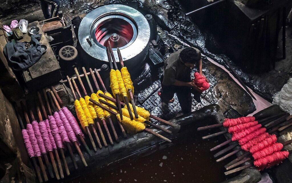 Des ouvriers teignent des fils dans un atelier traditionnel de teinture à la main dans le quartier séculaire de Darb al-Ahmar, au Caire, la capitale égyptienne, le 21 janvier 2020. (Crédit : Khaled DESOUKI / AFP)