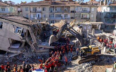Des secouristes sortent des corps des décombres d'un bâtiment après un tremblement de terre à Elazig, à l'est de la Turquie, le 26 janvier 2020. (Photo par BULENT KILIC / AFP)