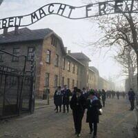 """Des survivants de la Shoah passent sous la porte portant l'inscription """"Le travail rend libre"""" après avoir déposé une gerbe au mur de la mort sur le site du mémorial de l'ancien camp de la mort nazi d'Auschwitz lors des cérémonies de commémoration du 75e anniversaire de la libération du camp à Oswiecim, en Pologne, le 27 janvier 2020. (Crédit : JANEK SKARZYNSKI / AFP)"""