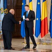Le président roumain Klaus Iohannis rend hommage à Traian Craciun, un survivant de la Shoah rom lors d'une cérémonie marquant le 75e anniversaire de la libération d'Auschwitz-Birkenau, le 27 janvier 2020, à Bucarest, en Roumanie. (Crédit : Andrei PUNGOVSCHI / AFP)