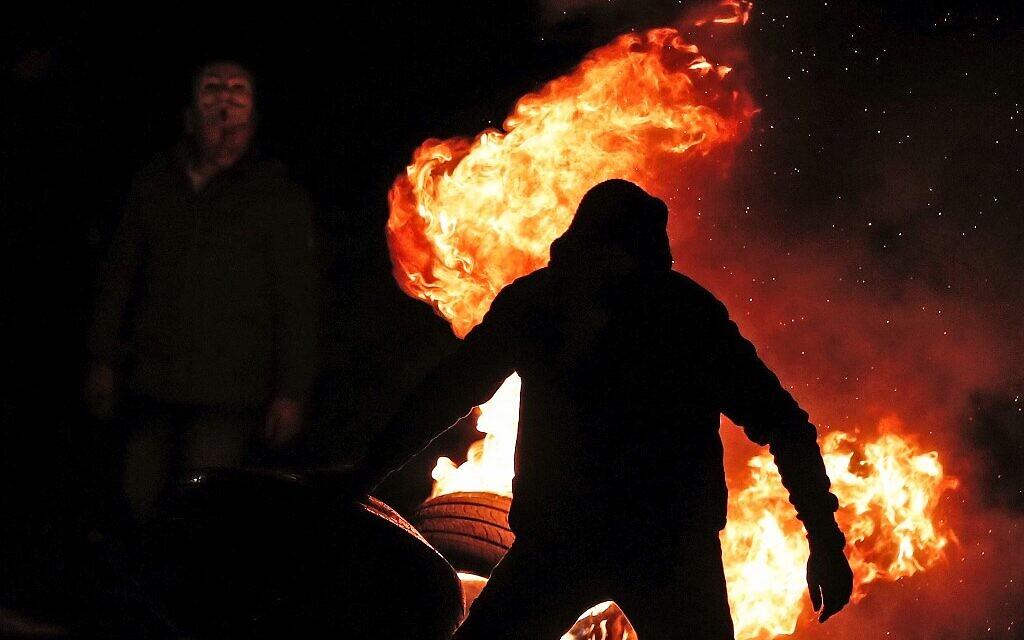 Des manifestants palestiniens brûlent des pneus pour protester contre la proposition de paix du président américain Donald Trump, le 28 janvier 2020, à l'entrée de la ville de Ramallah, en Cisjordanie. près de l'implantation juive de Beit El. (Crédit : Ahmad GHARABLI / AFP)