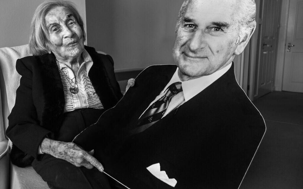 Judith Rosenberg, 93 ans, dans son appartement de Glasgow, en Écosse, tenant un carton découpé de son mari Harold, qui l'a trouvée et l'a libérée d'Auschwitz. (Crédit : Judah Passow/The Lonka Project)
