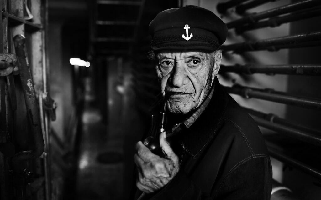 Yossi Weiss, 82 ans, est né en 1937 à Bratislava, en Slovaquie. Il a été transféré au camp de Zilina en 1941, et de là au camp de Novaky, tous deux en Slovaquie. Son père a été tué dans les camps et Yossi avait 5 ans lorsqu'il l'a vu pour la dernière fois. Lui et sa mère se sont enfuis dans les forêts et ont vécu cachés dans les forêts avec les partisans, souffrant du froid et d'une faim extrême. Après la guerre, ils sont retournés à Topoľčany où ils ont vécu dans une grande pauvreté, se déplaçant d'un endroit à l'autre. À l'âge de 11 ans, il fut à nouveau séparé de sa mère qu'il ne revit jamais. Il a immigré seul en Israël et s'est engagé dans la marine israélienne à l'âge de 17 ans. Il a passé 64 ans en mer et n'a cessé de naviguer qu'en 2018, l'année dernière. Yossi Weiss est marié à Michal et ils ont 4 enfants et vivent à Zichron Yaakov. Photographié sur un bateau dans le port de Haïfa en mai 2019 (Crédit : Eldad Rafaeli/The Lonka Project)