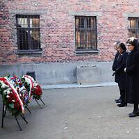 Sur cette image fournie par le consulat général des États-Unis à Cracovie, la présidente de la Chambre des représentants américaine Nancy Pelosi, au centre, et les présidents du Parlement polonais déposent des couronnes de fleurs sur le mur de la mort du camp de concentration nazi d'Auschwitz-Birkenau, lors d'une visite du site de l'ancien camp quelques jours avant le 75e anniversaire de sa libération par les troupes soviétiques en 1945, au musée d'Auschwitz-Birkenau, dans le sud de la Pologne, le mardi 21 janvier 2020. (Crédit : Consulat général des États-Unis à Cracovie via AP)