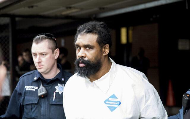 Des policiers de Ramapo escortent Grafton Thomas, le suspect de l'attaque de Monsey, depuis l'hôtel de ville de Ramapo jusqu'à un véhicule de police, à Ramapo (New York), le 29 décembre 2019. (Julius Constantine Motal/AP)