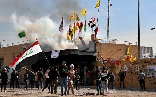 Des miliciens pro-iraniens et leurs partisans ont mis le feu tandis que des soldats américains tirent des gaz lacrymogènes lors d'un rassemblement devant l'ambassade des États-Unis à Bagdad, en Irak, le 1er janvier 2020. (Crédit : Khalid Mohammed / AP)