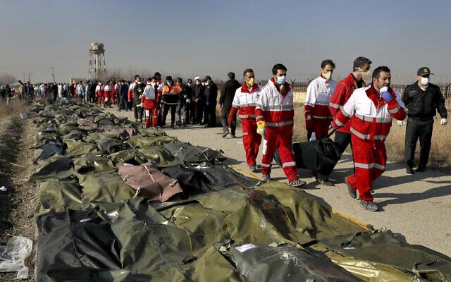 Des secouristes portent le corps d'une victime suite au crash d'un avion ukrainien à Shahedshahr, au sud-ouest de Téhéran, en Iran, le 8 janvier 2020 (Crédit : AP / Ebrahim Noroozi)