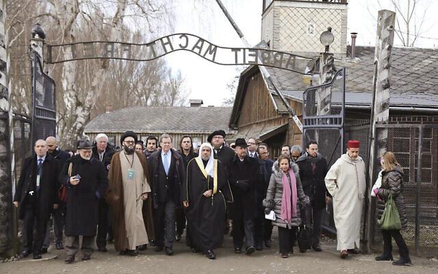 """Une délégation de responsables religieux musulmans à l'entrée du camp d'Auschwitz, accompagnée d'une organisation juive, lors de ce que les organisateurs ont décrit comme """"la délégation musulmane de plus haut rang"""" à visiter l'ancien camp de la mort nazi, à Oswiecim, en Pologne le 23 janvier 2020.  (American Jewish Committee via AP)"""