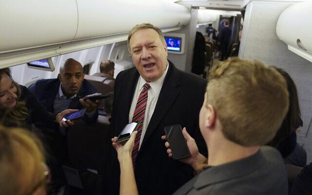Le secrétaire d'État américain Mike Pompeo s'adresse aux journalistes à bord de son avion en route pour Londres, le 29 janvier 2020. (Crédit : Kevin Lamarque/Pool via AP)