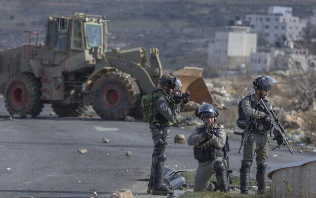 La police des frontières israélienne sécurisent une position tandis qu'un bulldozer de l'armée nettoie la route bloquée plutôt par des protestants palestiniens lors d'émeutes mineures, le 30 janvier 2020. (Crédit : AP Photo/Nasser Nasser)